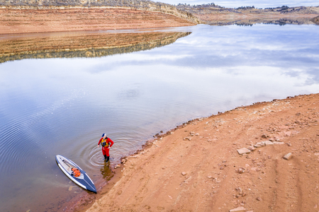 Aerial view of a stand up paddler in a drysuit on lake shore, typical winter scenery in northern Colorado foothills with no snow and low water level 스톡 콘텐츠