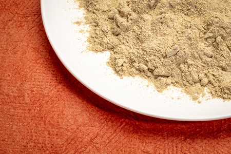 maca root powder on white ceramic plate against red textured paper