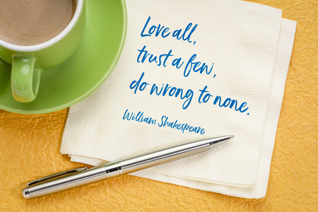 Love all, trust a few, do wrong to none -handwriting on a napkin with a cup of coffee