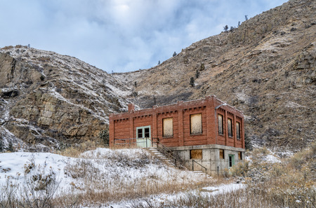 abandoned brick industrial building in a mountain winter scenery