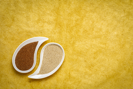 gluten free brown and ivory teff grain on teardrop shaped bowll against yellow textured paper - important food grain in Ethiopia and Eritrea Stock Photo