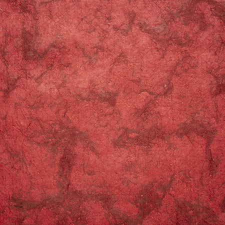 background of scarlet red  Huun Mayan handmade paper created  by Mayan artisans throughout the Yucatan Peninsula of Mexico