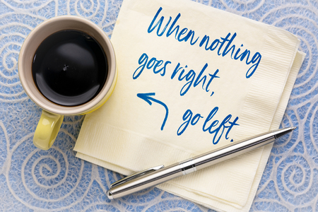 When nothing goes right, go left - handwriting on a napkin with a cup of coffee 版權商用圖片