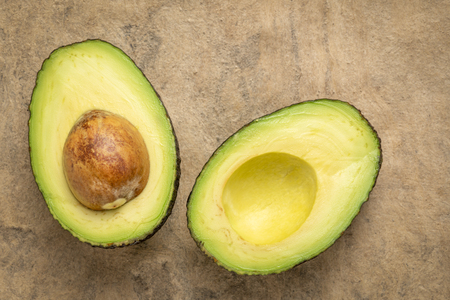 cut avocado fruit against buckskin amate bark paper with a copy space