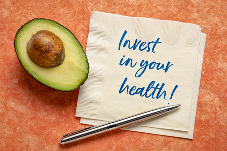 invest in your health - handwiring on napkin with a cut avocado against bark paper