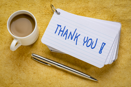 thank you - handwriting on a stack of index cards with a cup of coffee and  a pen