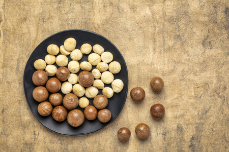 macadamia nuts on a black plate against buckskin textured paper background with a copy space Stock fotó