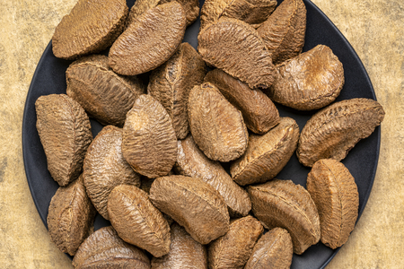 Brazilian nuts on a black plate against buckskin textured paper background with a copy space