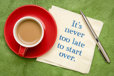 It is never too late to start over - handwriting on a napkin with a cup of coffee against colorful textured paper