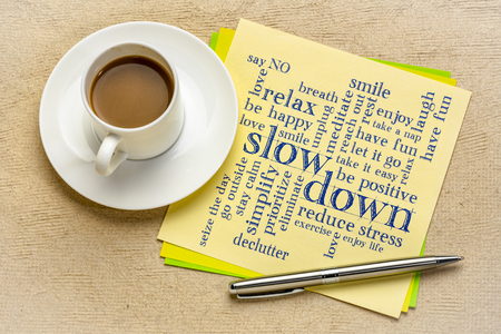 slow down and relax - reducing stress tips in a form of a word cloud on a square paper sheet with a cup of coffee