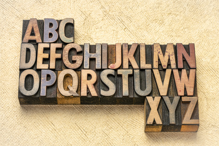 alphabet abstract in vintage letterpress wood type printing blocks against textured bark paper 写真素材