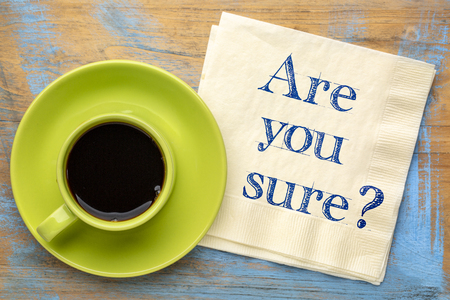 Are you sure? Handwriting on a napkin with a cup of coffee Фото со стока