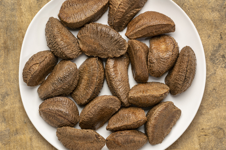 Brazilian nuts in shells on a white plate against textured bark paper background