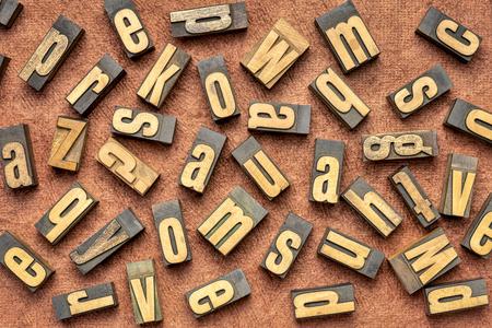 random letters overhead background - vintage letterpress wood type (inverted image)  against brown handmade bark paper Stok Fotoğraf