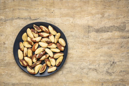 shelled  Brazilian nuts on a black plate against textured handmade paper background with a copy space