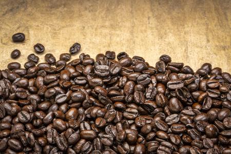 dark French roast coffee beans against textured bark paper Foto de archivo - 118199928