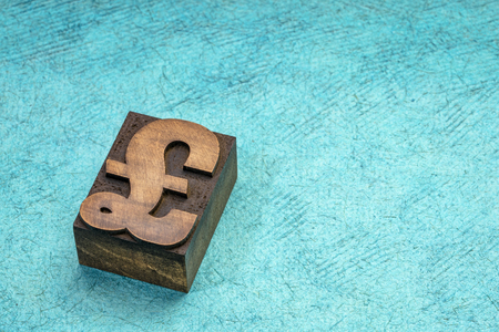 British Pound Sterling symbol in letterpress wood type printing block against turquoise handmade paper with a copy space Stock Photo