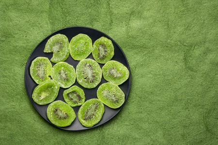 slices of dried kiwi fruit on a black plate against textured handmade bark paper with a copy space Stock Photo
