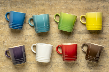 collection of colorful stoneware coffee cups against textured handmade bark paper