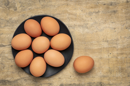 free-range large brown chicken eggs on a black plate against textured bark paper with a copy space