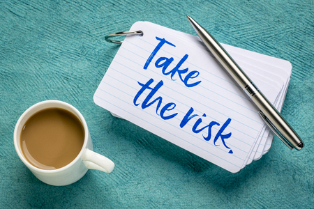 Take the risk - reminder on a stack of  index cards with a cup of coffee