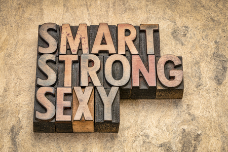 smart, strong, sexy word abstract in vintage letterpress wood type on textured bark paper
