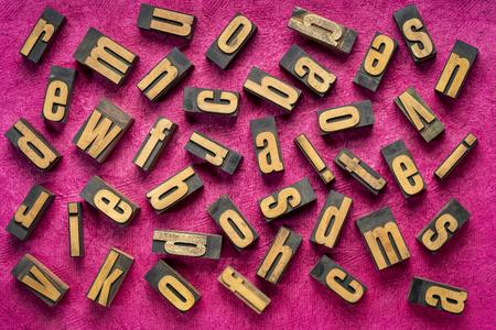 random letters overhead background - vintage letterpress wood type (inverted image)  against dark pink handmade bark paper