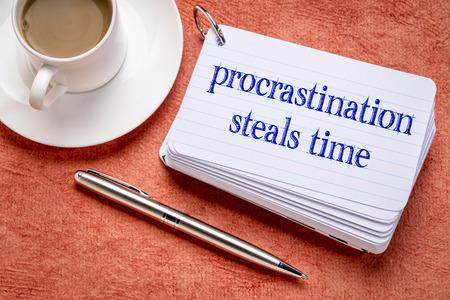 procrastination steals time reminder on a stack of  index cards with a cup of coffee Stock Photo