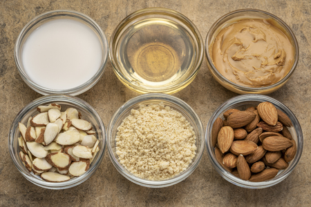 collection of almond super foods: nuts, flour, slices, milk, oils and butter - top view of small glass bowls over textured bark paper Stock Photo