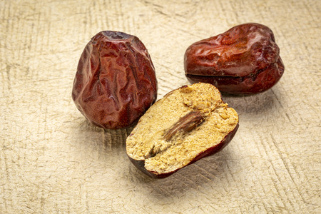 dried jujube fruits on textured bark paper Stock Photo