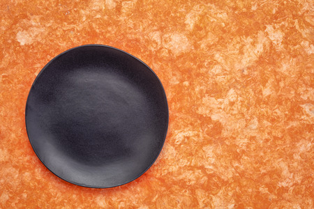 black ceramic plate with an irregular edge on an orange amate bark paper   with a copy space