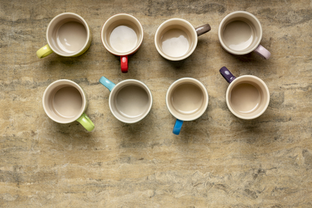 collection of empty colorful stoneware coffee cups against textured handmade bark paper with a copy space