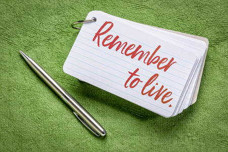 emember to live reminder - handwriting on an index card with a pen against green textured paper