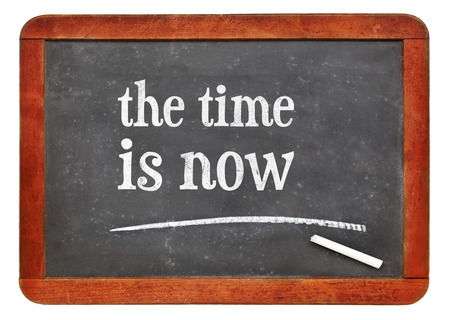 the time is now reminder - white chalk text on a vintage slate blackboard