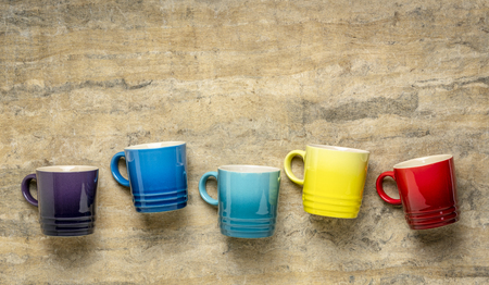 row of colorful stoneware coffee cups against textured handmade bark paper with a copy space Stock Photo