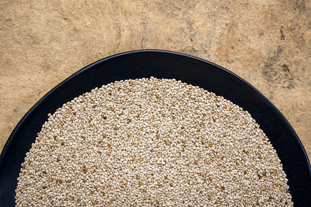 organic white chia seeds rich in omega-3 fatty acids,  top view of a black plate against textured bark paper