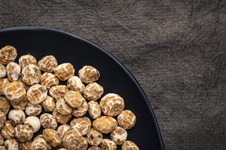 organic peeled tiger nuts, a rich source of resistant starch, top view on a black plate against textured bark paper Stock Photo