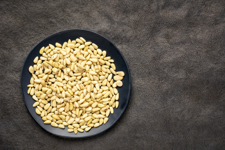 pine nuts with on a black plate, top view against black texture paper with a copy space