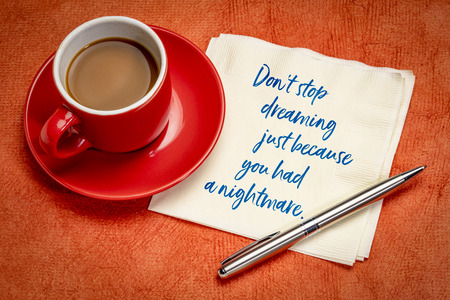 do not stop dreaming just beacause you had a nightmare - handwriting on a napkin with a cup of espresso coffee