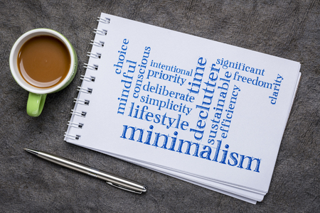 cloud of words associated to minimalism as a lifestyle - handwritingin an art sketchbook with acup of coffee Stock Photo