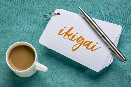 ikigai - Japanese concept  - a reason for being or a reason to wake up  - handwriting on a stack of index cards with a cup of coffee and a pen Stock Photo