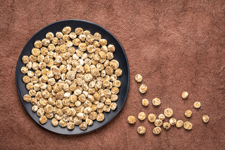 organic peeled tiger nuts, a rich source of resistant starch, top view on a black plate against textured bark paper with a copy space Stock Photo