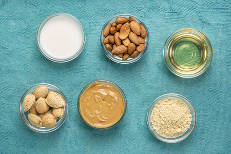 collection of almond super foods: nuts, flour,  milk, oils and butter - top view of small glass bowls over  turquoise textured bark paper