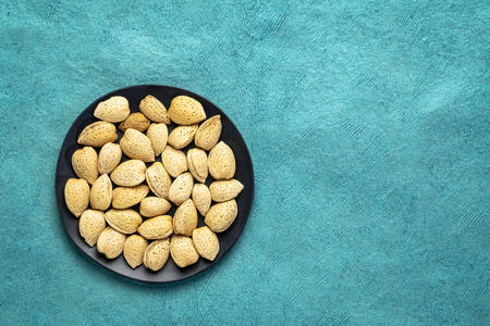 almond nuts in shells on a black plate against turquoise bark paper with a copy space