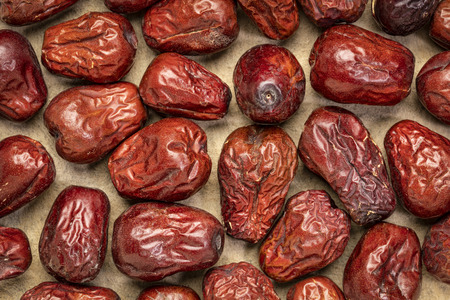 dried jujube fruits on textured bark paper, top view