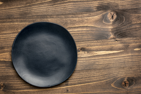 black ceramic plate with an irregular edge on a grained wood  with a copy space Stock Photo