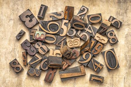 pile of random numbers in letterpress wood type against textured bark paper