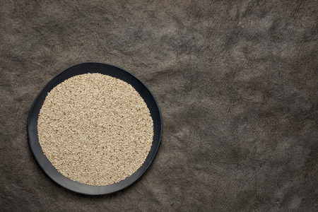 organic white chia seeds rich in omega-3 fatty acids,  top view of a black plate against textured bark paper with a copy space