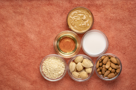 collection of almond super foods: nuts, flour,  milk, oils and butter - top view of small glass bowls over  orange textured bark paper