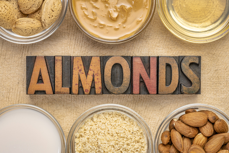 collection of almond super foods: nuts, flour, slices, milk, oils and butter - top view of small glass with almonds word in vintage letterpress wood type Stock Photo